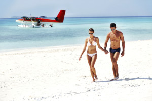 Attractive young couple walking on the beach with a seplane floating in the background
